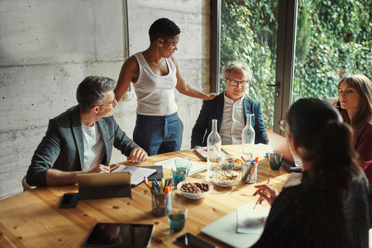 Black woman communicating with male colleagues during meeting