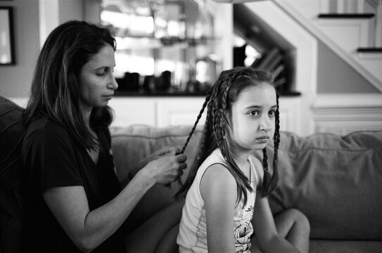 Mother braiding her daughter's hair while she watches television