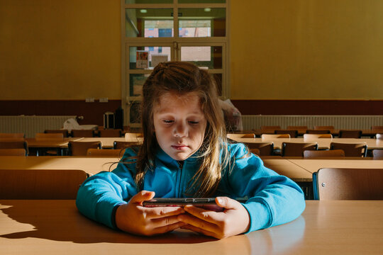 Little girl watching videos alone on phone in an empty classroom