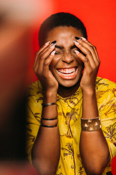 Beautiful Afro Woman posing over red laughing background smiling with eyes closed