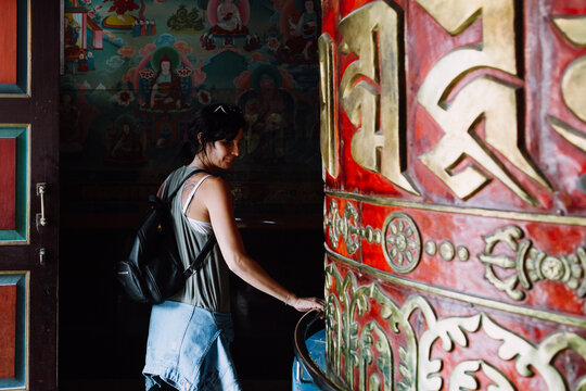 Woman spinning a big prayer wheel