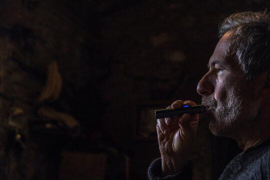 Lowkey of man smoking an electronic cigarette