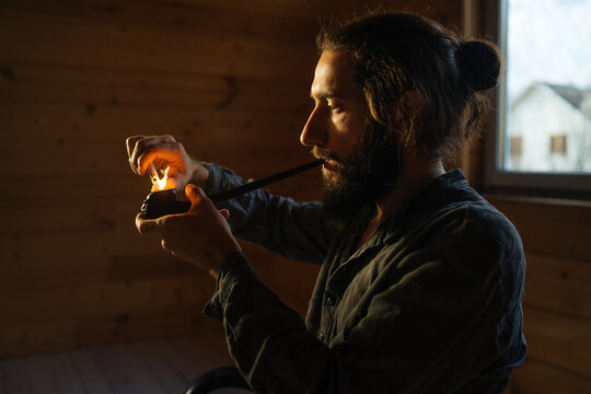 bearded man lights a pipe with a lighter in a dark room