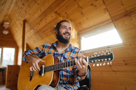 bottom view of a bearded long-haired man in a plaid shirt playing the guitar