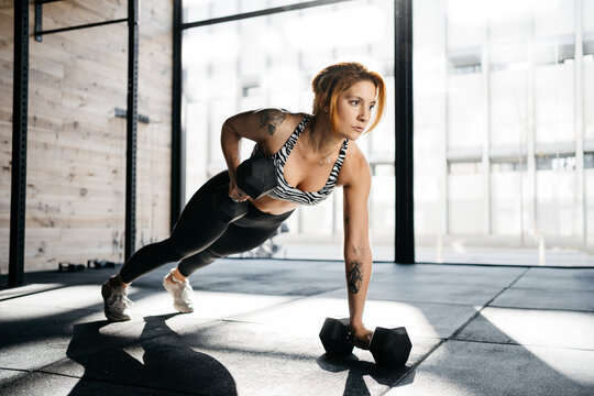 Woman exercising with dumbbells in a crossfit box