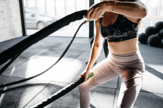 Anonymous women training with battle ropes in a crossfit box