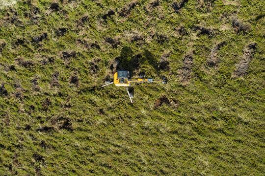 Machine digging holes for mass reforestation