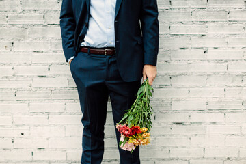 Body of a man over white brick wall holding a flower bouquet
