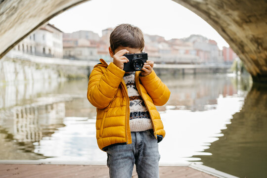 Kid taking photos with a film camera