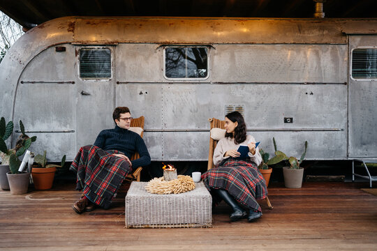 Adult couple enjoying time together at the porch of a travel trailer