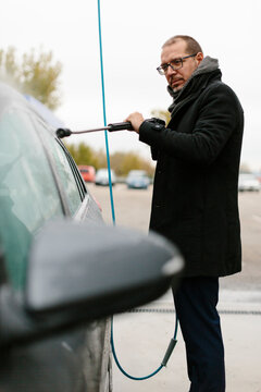 Man in suit washing his car