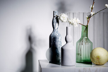 Still life of marble vases and Japanese cherry blossoms.
