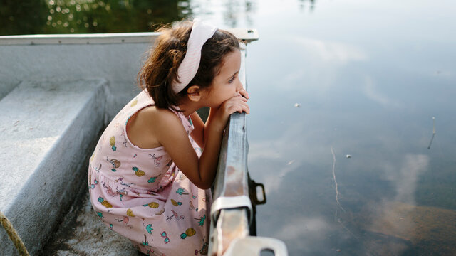 Kid on a boat in a lake