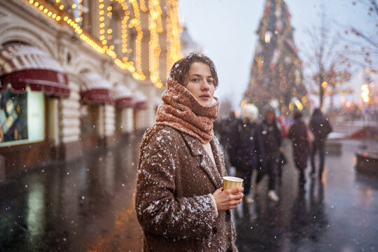 charming brown-haired woman on a snowy red square