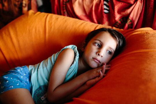 Kid lying on orange pillow