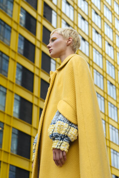 short-haired model in a yellow coat on a background of a yellow building