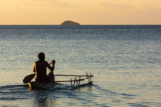 a man is paddling his outrigger canoe