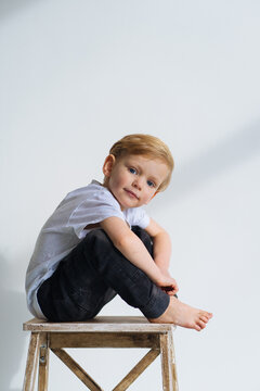 three-year-old blue-eyed boy blond sits on a chair