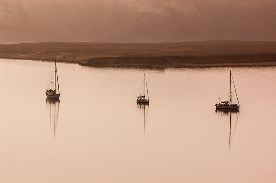 3 anchored boats in hazy light