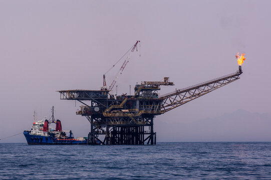 offshore oil rig with ship docked to it.