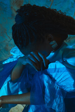 Sad black girl with braids and sleeves bows her head in a blue light