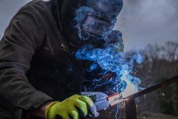 man welding, blue smoke