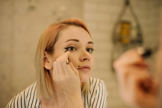 A portrait of a girl with piercing in a striped shirt who s drawing eyelines in front of the mirror