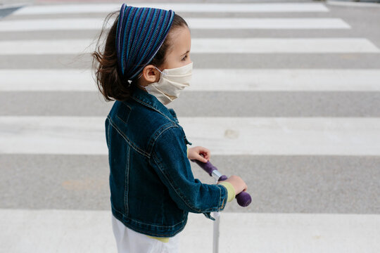 Kid with protective mask on scooter in pedestrian crossing
