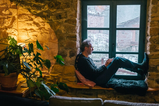 a man is sitting in a window seat in a stone rustic rural house