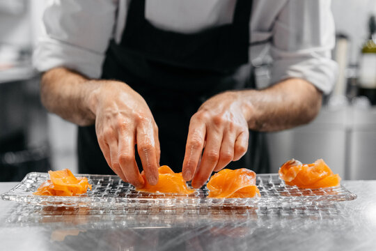 Anonymous chef preparing salmon dish