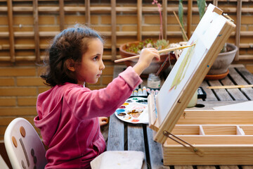 Little girl painting on an easel