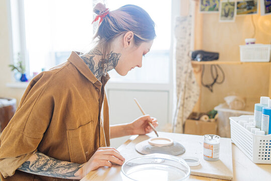 cute tattooed girl paints a plate of glaze