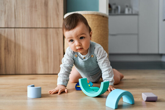 Baby playing on living room's floor