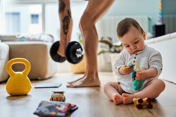 Anonymous father doing workout at home while his baby is playing at the living room