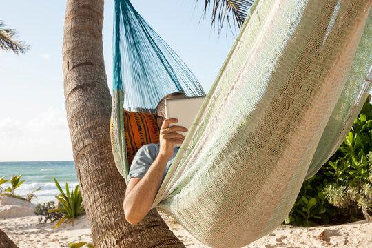Man looking at tablet in hammock