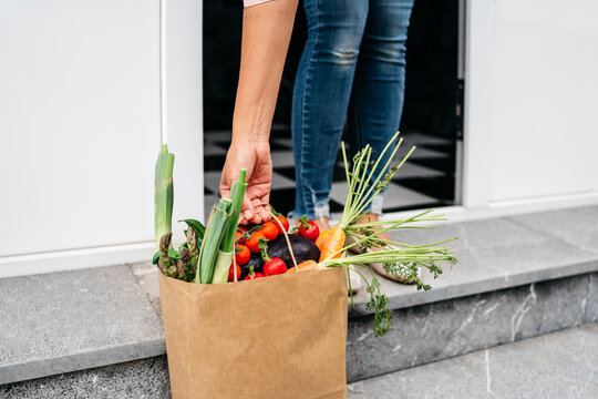 Anonymous woman picking up food delivery in paper bag from home porch