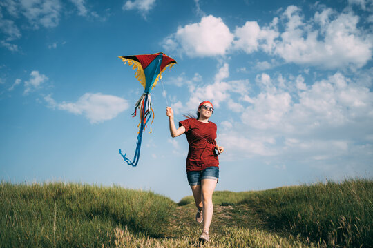 Young woman running with colorful flying kite