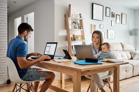 Young parents with baby working at home