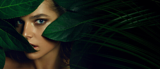 A beautiful tanned young woman with natural makeup and wet hair stands in the jungle among exotic plants. Tropical plants, nature.