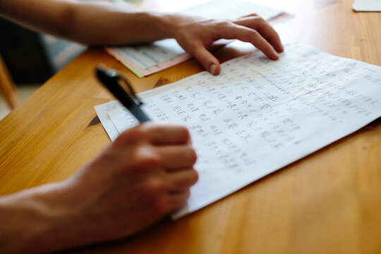 Anonymous hands writing Chinese words on a paper