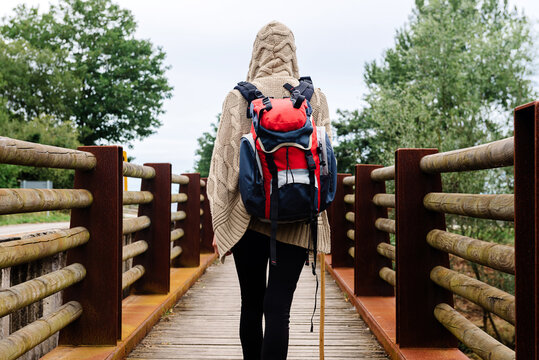 Back view of unrecognizable traveler with backpack and trekking stick walking alone on wooden footbridge during hiking through Spain