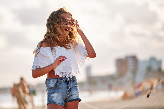 Low angle of delighted preteen girl with wavy hair dressed in stylish white top and denim shorts with sunglasses looking away while standing against blurred sea beach and enjoying summer holidays
