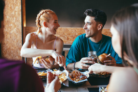 Happy young man and woman talking and laughing while gathering with friends in cafeteria and enjoying fast food snacks and drinks