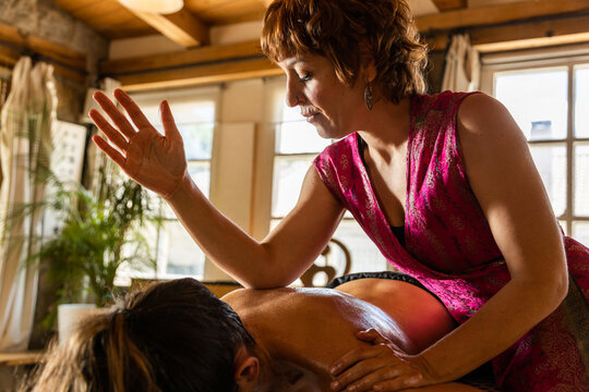 Professional massage therapist pressing oily back of anonymous relaxed client with elbows during session of ayurvedic massage in spa salon