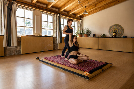 Female yoga instructor helping calm woman practicing mindfulness in Lotus pose in studio