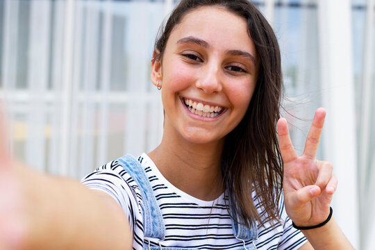 Delighted teen girl smiling for camera and showing V sign while taking selfie on modern city street