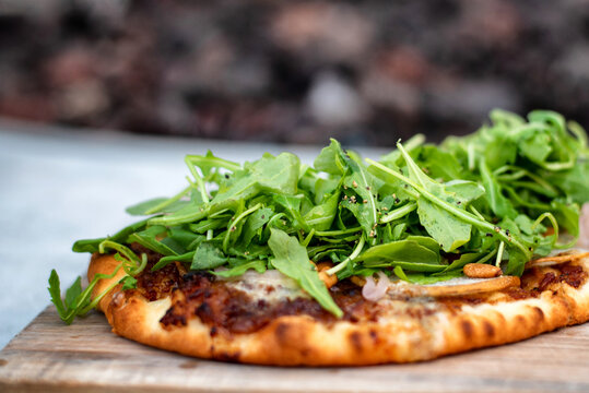 Closeup of flatbread pizza topped with arugula, pine nuts, pepper and various cheeses