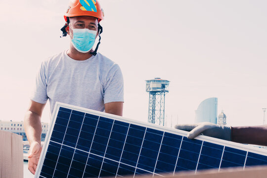 Workman in helmet and protective mask installing solar battery in industrial area of contemporary plant