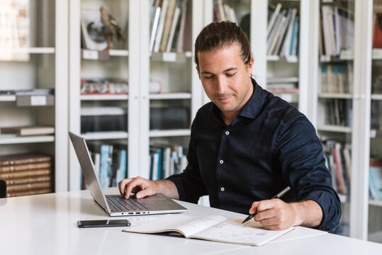 Focused businessman in formal shirt sitting at table while doing paperwork and typing on notebook in bright workspace