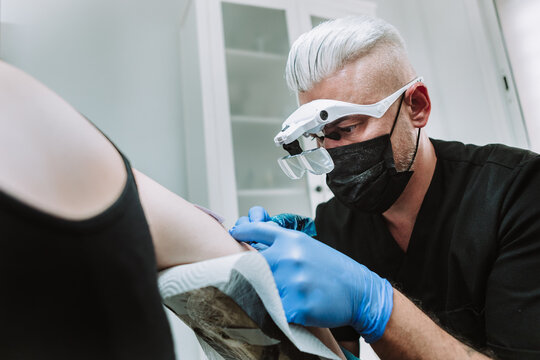 Busy male tattoo master in gloves and mask using machine with ink and creating picture on arm of client in salon